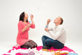Happy beautiful pregnant woman and her husband blowing soap bubb women bubbles in studio Stock Photography