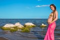 Happy beautiful pregnant woman in swimsuit relaxing at beach Royalty Free Stock Images