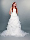 Happy beautiful red haired bride on gray background wedding day portrait of blue eyed long white dress in full length studio shot Royalty Free Stock Image