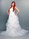 Happy beautiful red haired bride on gray background wedding day portrait of blue eyed long white dress in full length studio shot Stock Image