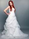 Happy beautiful red haired bride on gray background wedding day portrait of blue eyed long white dress in full length studio shot Royalty Free Stock Photography