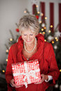 Happy beautiful senior with a christmas gift woman smiling as she looks down at she is holding in her hands Stock Photos
