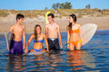 Happy beautiful teen surfers enjoying on beach talking shore smiling Royalty Free Stock Images