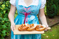 Happy beautiful woman in dirndl dress holding pretzel girl oktoberfest hands Royalty Free Stock Images