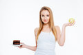Happy beautiful woman holding chocolate cake and green apple