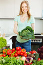 Happy beautiful woman with raw vegetables and greens in home kitchen Stock Photo
