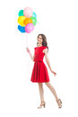 Happy beautiful woman in red dress holding colorful balloons Royalty Free Stock Photo