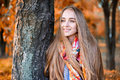 Happy beautiful woman standing near the tree in the autumn park Royalty Free Stock Image