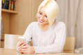 Happy beautiful woman texting on her smartphone at home Royalty Free Stock Photos