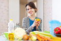 Happy beautiful woman with vegetables in her kitchen at home Royalty Free Stock Images