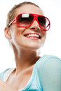 Happy beautiful woman with a vivacious smile low angle portrait of wearing sunglasses isolated on white Stock Image