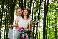 Happy beautiful young couple on bicycle in a summer park Stock Image