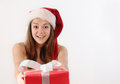 Happy beautiful young girl in santa hat giving you a gift for ch smiling with gifts christmas holiday concept Stock Photos