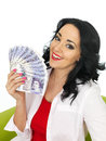 Happy beautiful young hispanic woman holding a fan of money with features in her twenties smiling winning cash savings loan Stock Photography