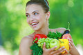 Happy beautiful young woman portrait of with vegetables against background of summer green park Royalty Free Stock Photo