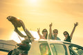 Happy best friends cheering by car road trip at sunset group of people outdoor on vacation tour friendship concept travel with Royalty Free Stock Images