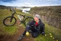 Happy biker on backdrop of waterfall in mountains Iceland