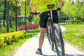 Happy biker ride on road in summer city park. Sport relax concept Royalty Free Stock Photo