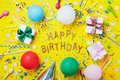 Happy birthday background or greeting flyer. Colorful holiday supplies on yellow table top view. Flat lay style. Royalty Free Stock Photo
