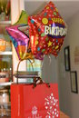 Happy birthday colorful balloons and package from edible arrangements Royalty Free Stock Photos
