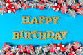 Happy birthday golden text and silver and red gifts on a blue Royalty Free Stock Photo