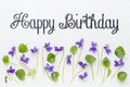 Happy birthday greetings with viola flowers fresh and leaves on white art canvas Stock Photos