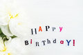 Happy Birthday Letters Cut out from Magazines and White Peonies Royalty Free Stock Photo