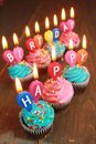 Happy birthday pink and blue icing cupcakes with candles saying Royalty Free Stock Photo