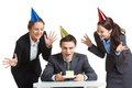 Happy birthday portrait of young businessman in cap looking at piece of cake with two joyful females near by Stock Images