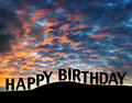 Happy birthday a sign silhouetted on a hillside with dramatic sunset or sunrise clouds Stock Photo