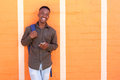 Happy black guy laughing with cell phone against orange wall Royalty Free Stock Photo