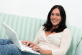Happy black haired woman using a laptop Royalty Free Stock Photography