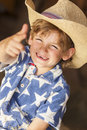 Happy blond boy child cowboy hat star shirt young smiling wearing a blue and sitting on hay or straw bales making a finger gun Stock Photography