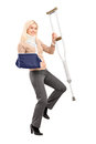 Happy blond female with broken arm holding a crutch Royalty Free Stock Photos