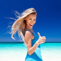 Happy blond girl on beach, showing okey sign. Stock Photography
