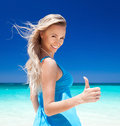 Happy blond girl on beach showing thungs up vacation concept Stock Photography
