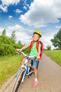 Happy blond girl with braids in bicycle helmet rides a bike on the path the forest summer Stock Images