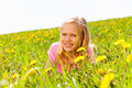 Happy blond girl in the meadow with flowers yellow summer Stock Image