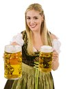 Happy blond serving beer during oktoberfest photo of a beautiful woman wearing traditional dirndl smiling and holding huge beers Royalty Free Stock Images