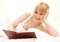 Happy blond student girl in bed reading book Stock Image