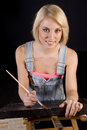 Happy blond woman dressed overalls provides finishing touches to painting easel Royalty Free Stock Photography