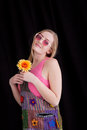 Happy blond woman holding yellow flower in hippy outfit isolated on black background Royalty Free Stock Images