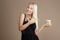 Happy Blond Woman Points Out to the Cup of Coffee Royalty Free Stock Photo
