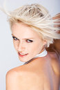 Happy blond woman with a quirky hairstyle as her spiky hair blows off her forehead straight up into the air high angle portrait on Royalty Free Stock Photography
