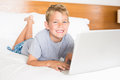 Happy blonde boy lying on bed using laptop Royalty Free Stock Photo