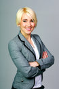 Happy blonde businesswoman with arms folded standing on a gray background Royalty Free Stock Images