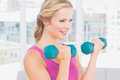 Happy blonde lifting dumbbells at home in the living room Royalty Free Stock Photos