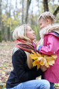 Happy blonde mother with maple leaflets looks at daughter yellow her in autumn forest shallow depth of field focus on woman Royalty Free Stock Image