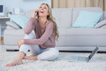 Happy blonde sitting on carpet phoning at home in the living room Stock Image