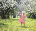 Happy blonde toddler girl having fun dancing in the park Stock Photography